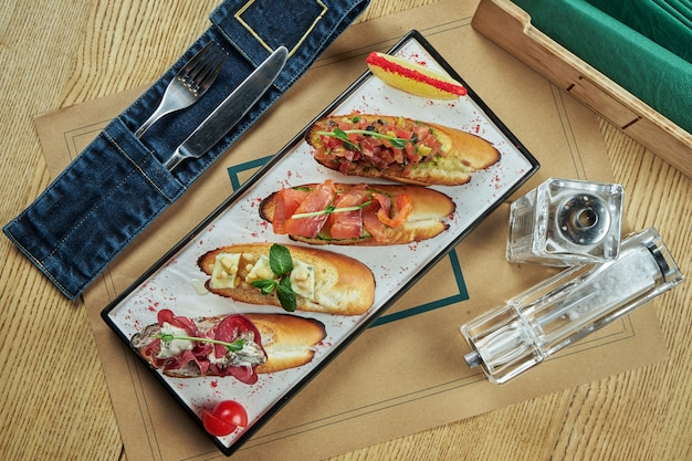 Bruschetta varia assortita su un piatto bianco. baguette bianche con jamon, toast con salsa di pomodoro, bruschette con salmone e gorgonzola. tavolo da ristorante. vista dall'alto