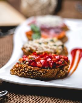 Bruschetta vista frontale con semi di sesamo e pomodori