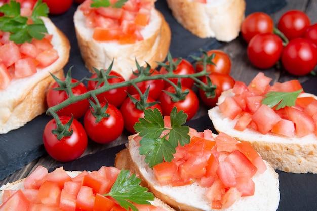 Bruschette italiane tradizionali con i pomodori ciliegia sul piatto di pietra