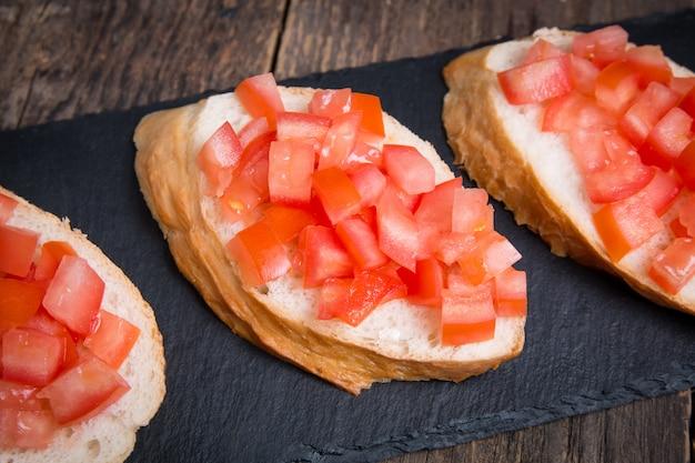 Bruschette italiane tradizionali con pomodorini sul piatto di pietra
