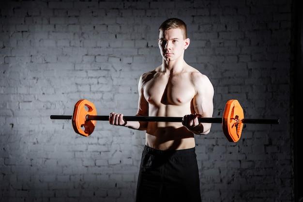 Brutal bodybuilder uomo atletico con abs perfetto, spalle, bicipiti, tricipiti e petto.