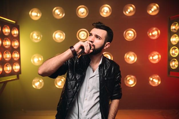 Brutale cantante barbuto con microfono sul palco con decorazioni di luci