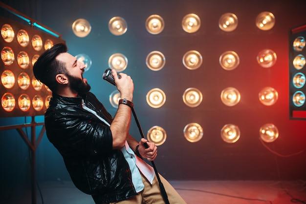 Brutale cantante barbuto con microfono sul palco