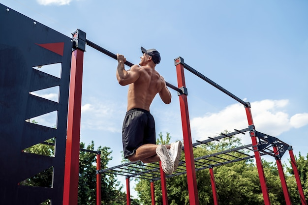 Brutale uomo atletico che fa esercizi di pull-up su una traversa.