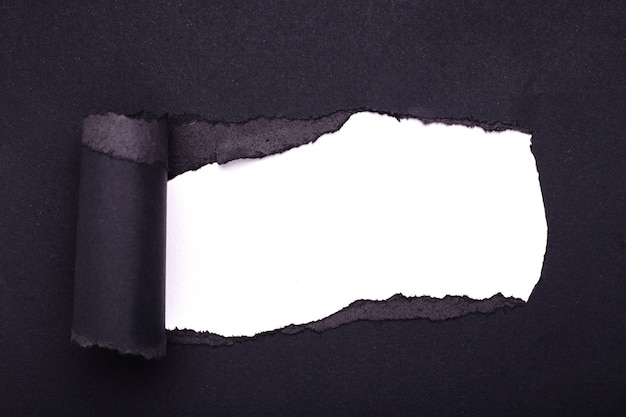 Buco nella carta nera. strappato. carta bianca . astratto.