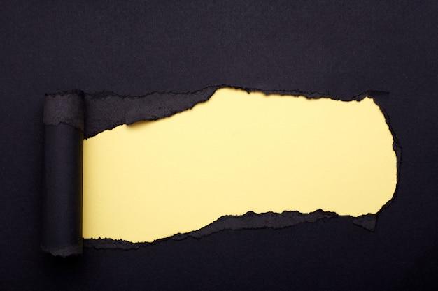 Buco nella carta nera. strappato. carta gialla. astratto.