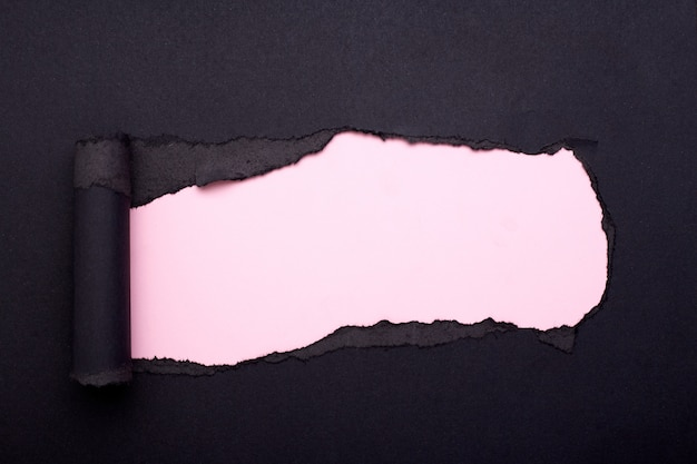 Buco nella carta nera. strappato. carta rosa. astratto.