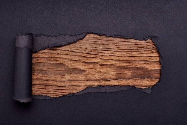 Buco nella carta nera. strappato. di legno. astratto.