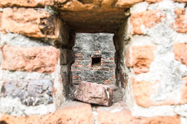 Buco nella distruzione vecchia trama di muro di cemento