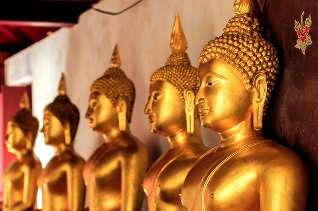 Buddha dorato del primo piano con morbido-focud e sopra luce nei precedenti