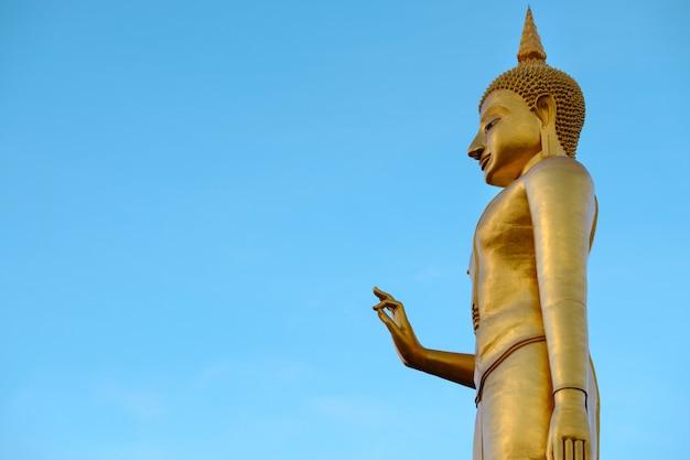 Buddha dorato sul backgrond del cielo blu con lo spazio della copia