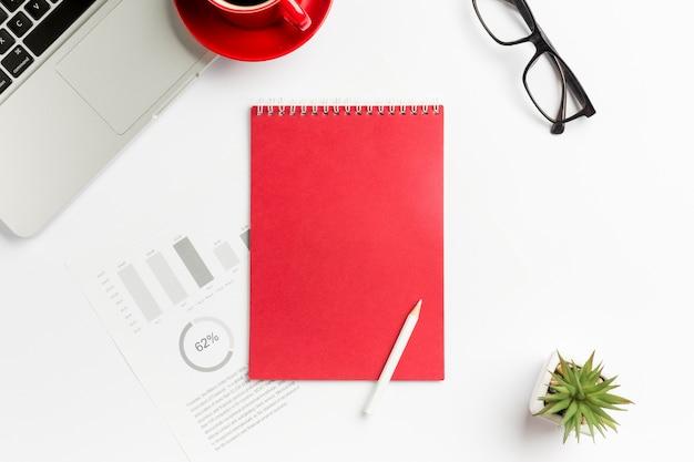 Budget grafico, blocco note a spirale, matita, pianta di cactus, laptop e occhiali su sfondo bianco
