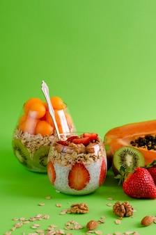 Budini di chia con frutta fresca cruda tropicale con fiocchi d'avena e noci per mangiare sano sul verde