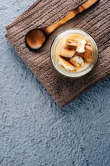 Budino alla vaniglia saporito su fondo di legno blu.