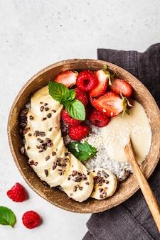 Budino di chia con bacche, banana, burro d'arachidi e cacao in una ciotola di guscio di noce di cocco
