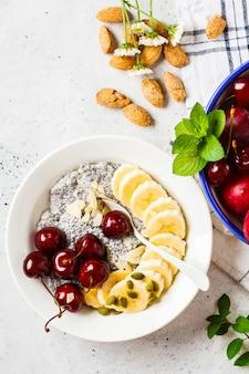 Budino di chia con banana, ciliegia e noci in piatto bianco.