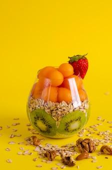 Budino di chia con kiwi, fiocchi d'avena e palline di melone o papaia in un bicchiere giallo