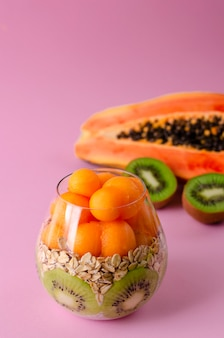 Budino di chia con kiwi, fiocchi d'avena e palline di papaia in un bicchiere viola