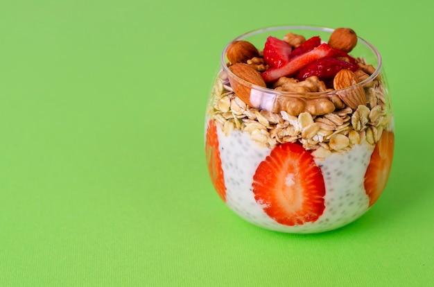 Budino di chia yogurt con fragole fresche, avena e noci in un bicchiere sul verde