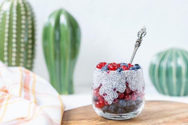 Budino di semi di chia con mirtilli e bacche di ribes in un bicchiere