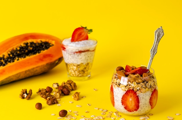 Budino di yogurt con fragole, fiocchi d'avena e noci in un bicchiere giallo