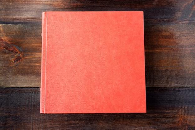 Bugia rossa dell'album di nozze sulla tavola di legno marrone