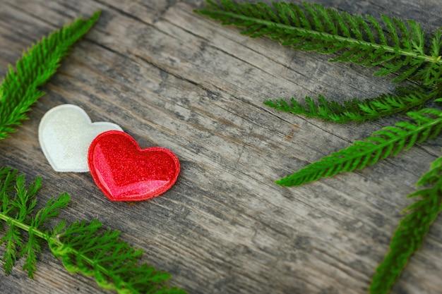 Bugia rossa e bianca del cuore su fondo di legno