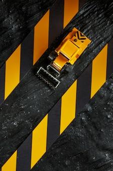 Bulldozer giocattolo giallo. nastro per recinzione nero e giallo