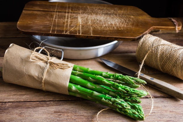 Bundle di asparagi organici freschi avvolti in carta del mestiere sul tavolo della cucina