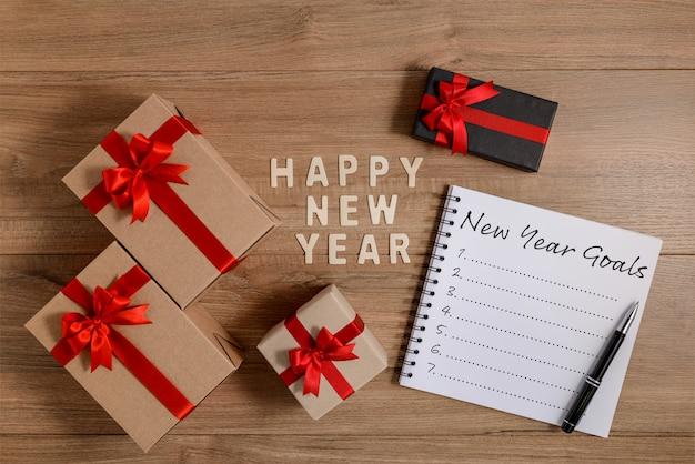 Buon anno 2020 elenco di obiettivi in legno e capodanno scritti su notebook con confezione regalo