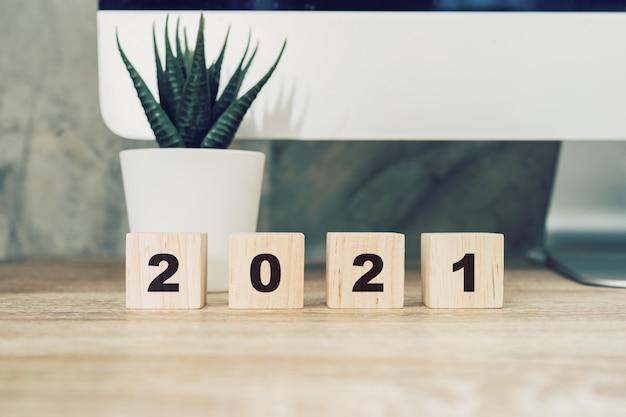 Buon anno 2021 sul blocco di legno sul desktop tavolo e sulla pianta da vaso di legno. concetto di nuovo anno