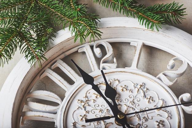 Buon anno a mezzanotte, orologio in legno vecchio e rami di abete