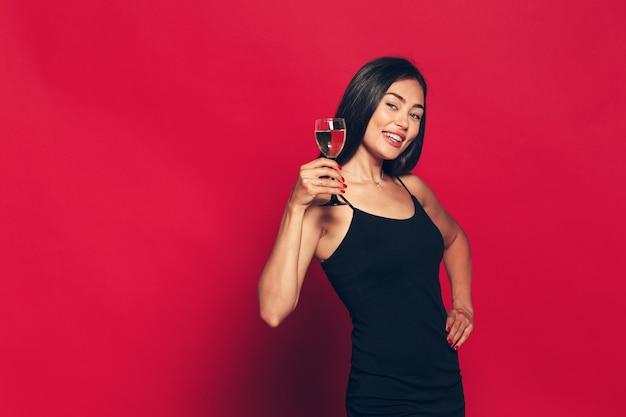 Buon anno a te. una giovane e bella donna che balla con un bicchiere di champagne