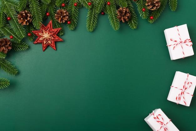 Buon anno, rami di albero di abete piano di vista superiore di giorno superiore di natale, contenitore di regalo e decorazione su verde