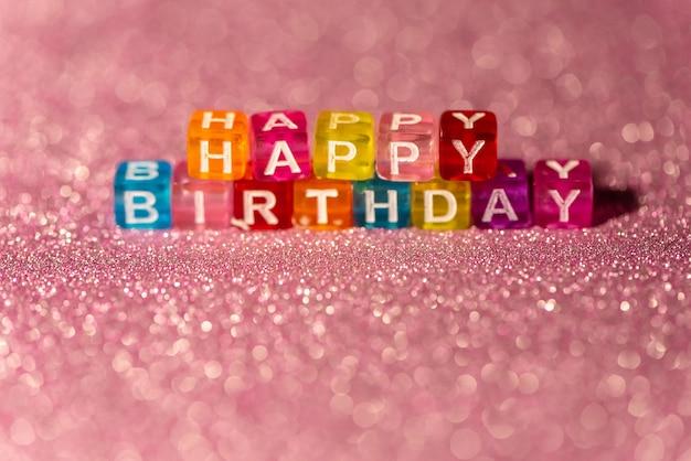 Buon compleanno con stampatello colorato su sfondo rosa glitter. cartolina per festeggiare.