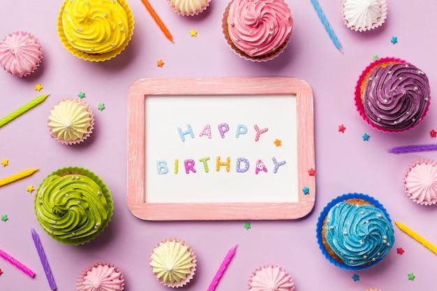 Buon compleanno in legno su una lavagna bianca circondata da muffin; aalaw; candele e spruzza su sfondo rosa