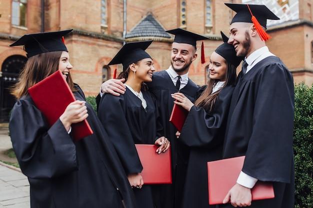 Buon giorno della laurea. 5 laureati tengono in mano i suoi diplomi di laurea