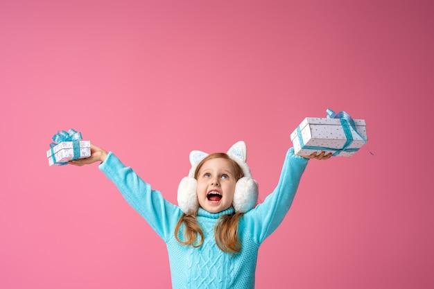 Buon natale! bambina in cuffie di pelliccia con scatole regalo nelle sue mani