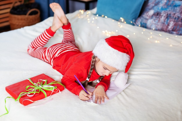 Buon natale. capodanno 2020! bambina in pigiama rosso e cappello di babbo natale scrive lettera a babbo natale in camera da letto