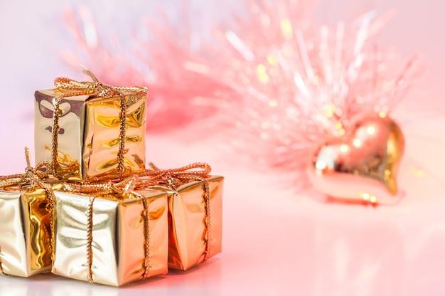 Buon natale, capodanno, regali in scatole d'oro e un cuore d'oro su uno sfondo di bokeh rosa e giallo.