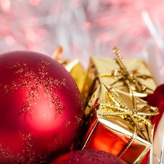 Buon natale, capodanno, regali in scatole d'oro su uno sfondo di bokeh rosa e giallo.