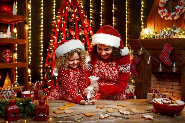 Buon natale e buone feste. bambina riccia sveglia allegra e sua sorella maggiore in cappelli di santa che cucinano i biscotti di natale.