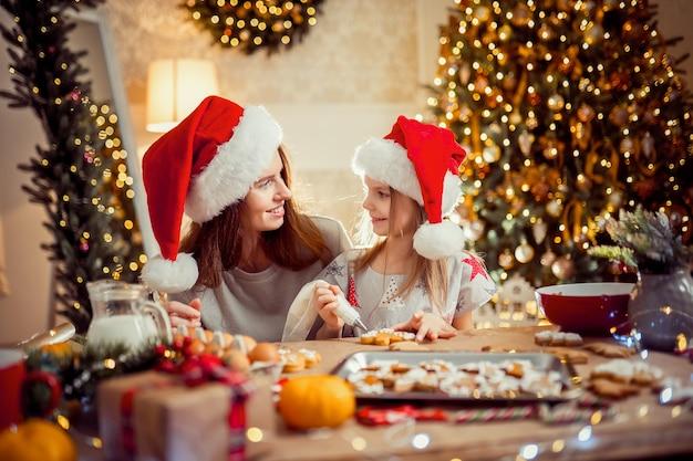 Buon natale e buone feste. madre e figlia che cucinano i biscotti di natale.