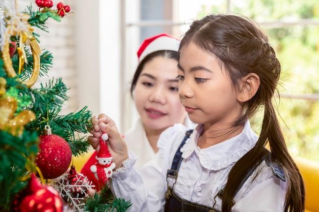 Buon natale e buone feste! mamma e figlia stanno decorando l'albero di natale in casa.