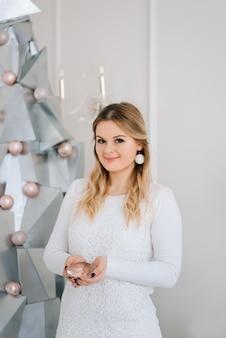Buon natale e felice anno nuovo. bella ragazza vicino all'albero di natale d'argento moderno del metallo