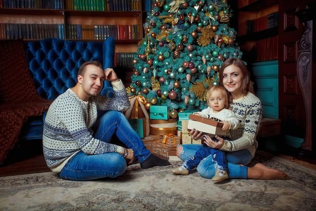 Buon natale e felice anno nuovo! famiglia felice che celebra le vacanze invernali a casa