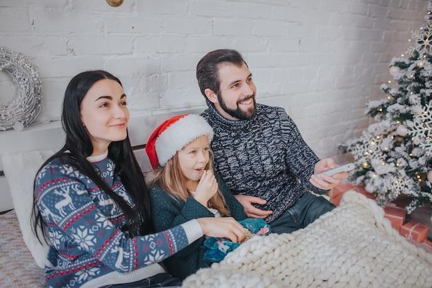 Buon natale e felice anno nuovo . giovane famiglia che celebra la vacanza a casa. il padre tiene il telecomando dalla tv. papà, figlia e madre guardano la televisione.