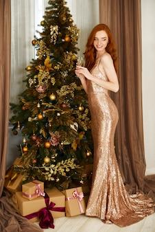 Buon natale e felice anno nuovo! la giovane donna sveglia allegra sta l'albero di festa vicino con i presente.