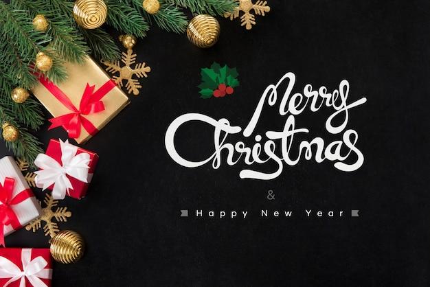 Buon natale e felice anno nuovo testo con scatole regalo e ornamenti sulla lavagna