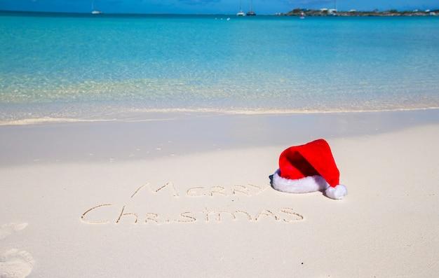 Buon natale scritto sulla sabbia bianca della spiaggia tropicale con cappello di natale